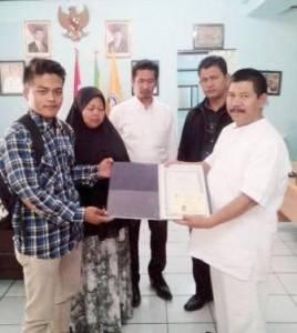 BEBAS TUNGGAKAN: Kepsek SMKN 6 Bandung Ramdan, menyerahkan ijazah asli milik Taofik Hamdani kemarin (24/7).