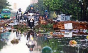 Pengendara bermotor menghundari tumpukan barang dagangan yang rusak akibat banjir di Pasar Gedebage, Jalan Soekarno-Hatta, Kota Bandung, Rabu (8/6).