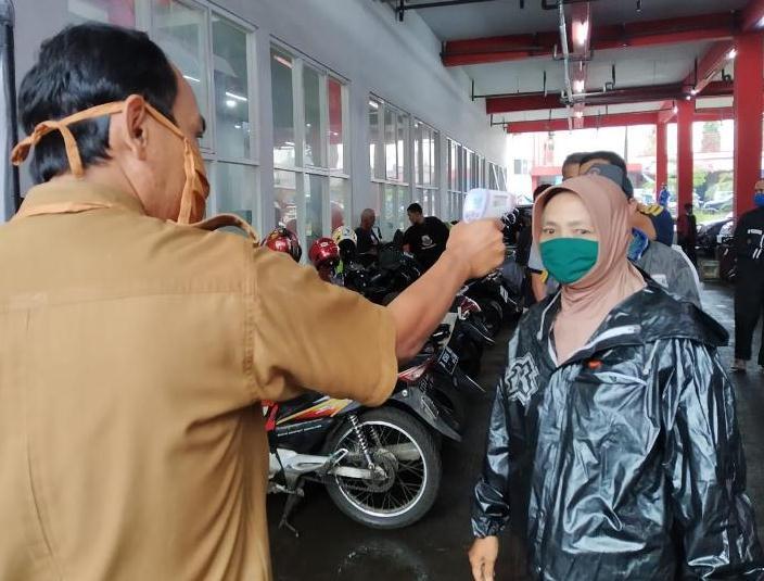 ILUSTRASI :Petugas dari UPTD Pasar memeriksa suhu pengunjung sebelum memasuki area Pasar Atas Baru. Pengecekan tersebut sebagai salah satu upaya Pemkot Cimahi, mencegah penularan virus korona di Cimahi.