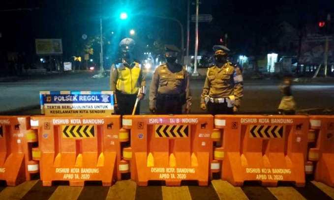 Petugas Kepolisian tampak sedang berjaga disalah satu ruas jalan yang terkena rekayasa penutupan mulai pukul 21.00 hingga 06.00 WIB.