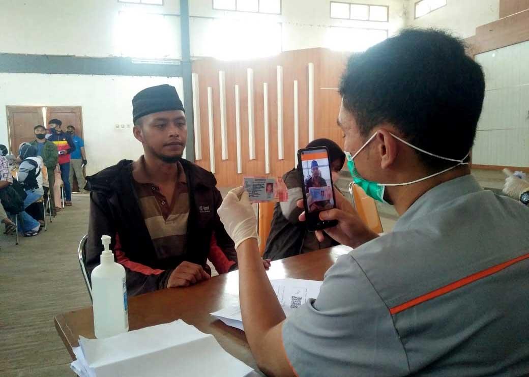 Petugas dari PT POS sedang memeriksa KTP milik warga (Ilustrasi/Dok Jabarekspres.com)
