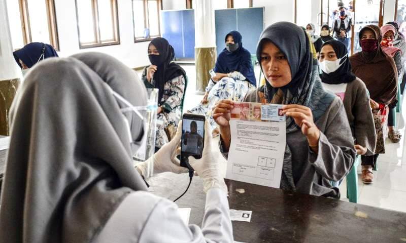 ILUSTRASI: Petugas memotret identitas penerima bantuan sebagai tanda bukti saat penyaluran bansos. (FOTO ANTARA/ILUSTRASI)