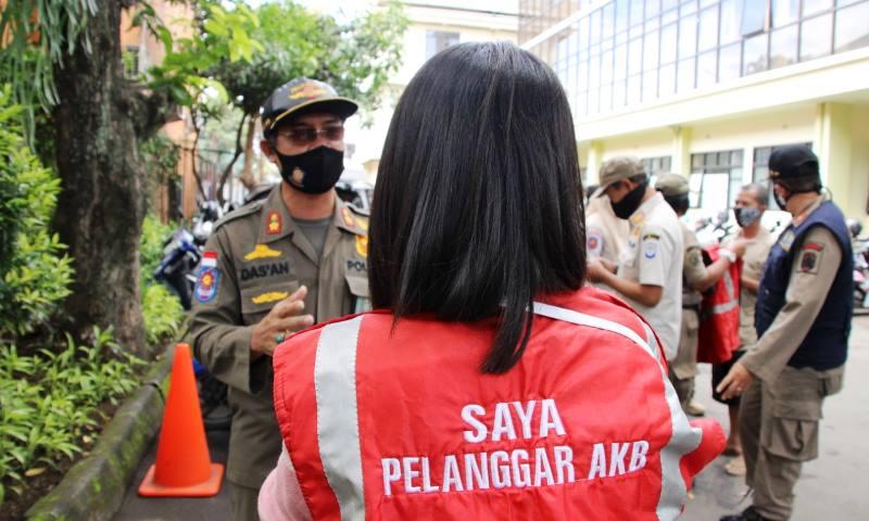 Seorang warga yang kedapatan tidak menggunakan masker saat beraktivitas di luar mendapat hukuman dari para petugas yang sedang melaksanakan razia protokol kesehatan.