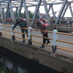 Petugas Polisi dan TNI sedang mengecek badan jembatan yang mengalami keretakan