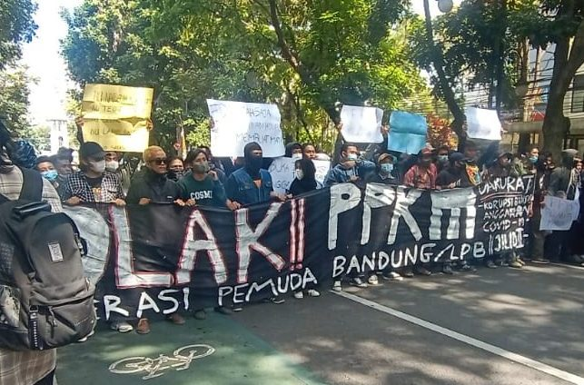 Para demonstran membentangkan banner bertuliskan penolakan terhadap diperpanjangnya PPKM Darurat.