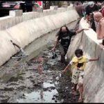 Warga saat mengambil kaos dari Presiden Jokowi yang jatuh ke irigasi di Cirebon, Jawa Barat, Selasa (31/8/2021). (ANTARA/Ho-Riri)
