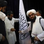 Pejabat Taliban mengatur bendera Taliban, sebelum konferensi pers oleh juru bicara Zabihullah Mujahid di Pusat Informasi Media Pemerintah, Kabul, Afghanistan, Selasa (17/8). Foto: Rahmat Gul/AP Photo