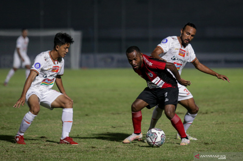 Pesepak bola Persipura Jayapura Yohanes Pahabol (tengah) berebut bola dengan pesepak bola Persija Jakarta Rohit Chand (kanan) pada laga lanjutan Liga 1 2021-2022 di Stadion Indomilk Arena, Tangerang, Banten, Minggu (19/9/2021). . ANTARA FOTO/Fauzan/wsj (ANTARA FOTO/FAUZAN)