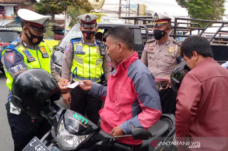 Sejumlah personel polisi membagikan masker kepada pengendara sepeda motor di Jalan Bunderan Suci, Kabupaten Garut, Jawa Barat, Senin (20/9/2021). (ANTARA/Feri Purnama)