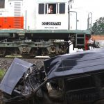 Dokumentasi. Sebuah kereta api melintas di depan bangkai mobil minibus bernopol N 1447 CP yang ringsek usai ditabrak kereta api di perlintasan tanpa palang pintu di Sonotengah, Malang, Jawa Timur, Rabu (27/10/2021). . ANTARA FOTO/Ari Bowo Sucipto/foc.