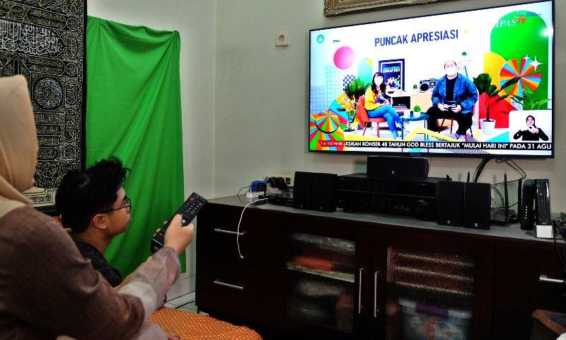 Seorang remaja menyaksikan siaran televisi didampingi orang tua. Siaran TV Digital hadir membawa beragam fitur diantaranya Parental Lock. (Foto: Ilustrasi)