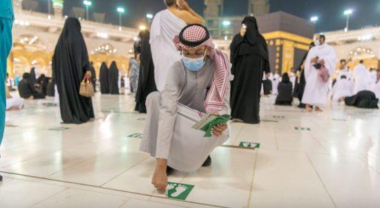 Petugas di Masjidil Haram Makkah membuka tanda stiker jaga jarak bagi para jamaah
