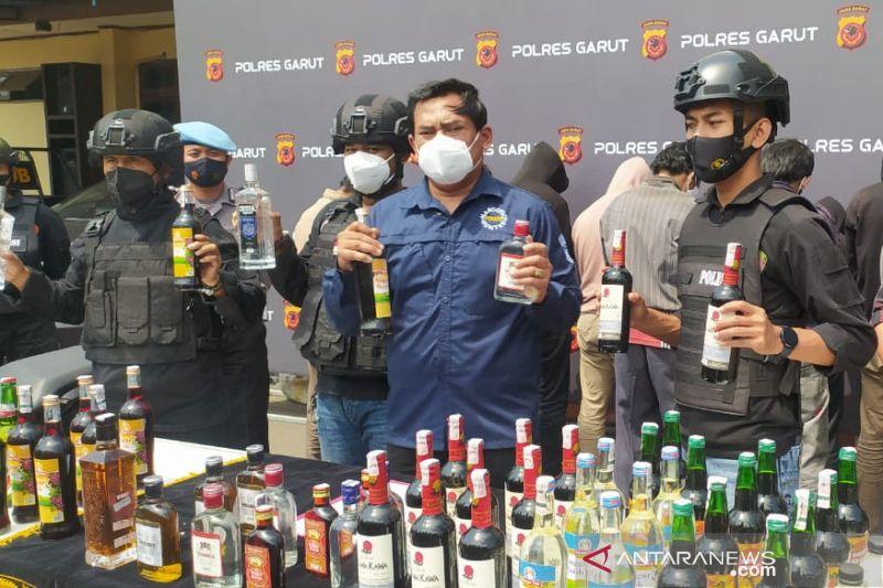 Polisi menunjukkan barang bukti minuman keras dan penjual hasil operasi pemberantasan minuman keras di Kabupaten Garut, Jawa Barat, Selasa (12/10/2021). (ANTARA/Feri Purnama)