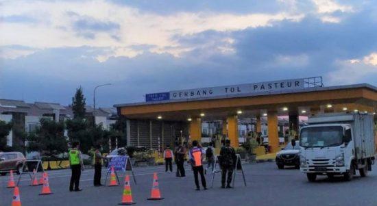 Petugas kepolisian memberlakukan sistem ganjil-genap di Gerbang Tol Pasteur, Kota Bandung, Jawa Barat. (ANTARA/Bagus Ahmad Rizaldi)
